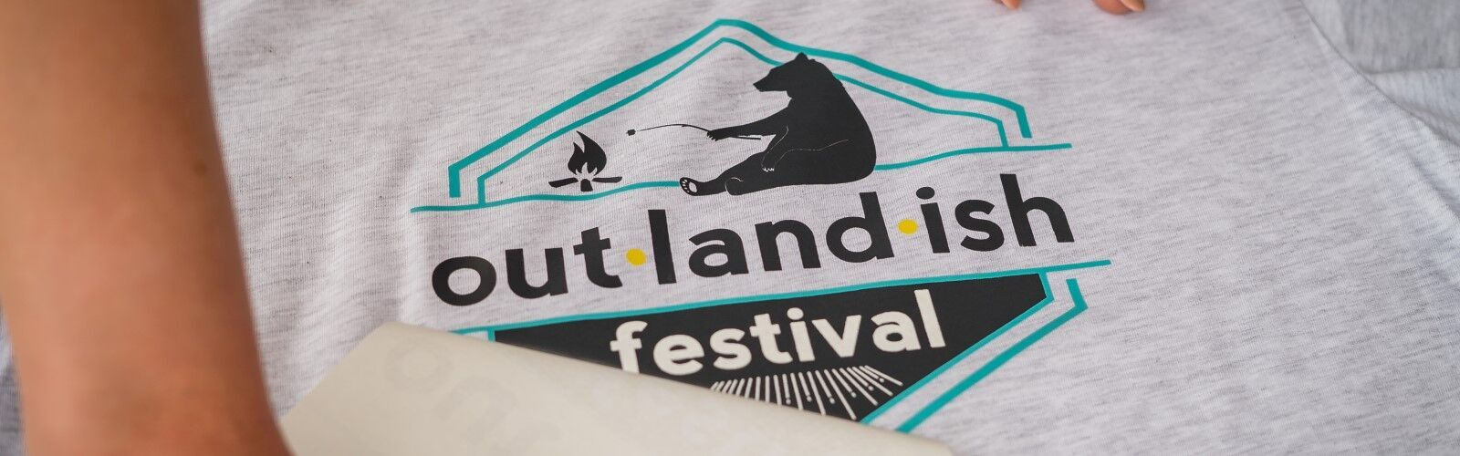 out·land·ish festival t-shirts being printed by Red Threads