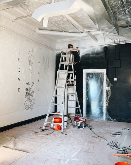 Lyndsay Edmonds, owner of Harless + Hugh Coffee as she paints the cafe with a new coat of white. (PC: Julia Ross/Harless + Hugh)