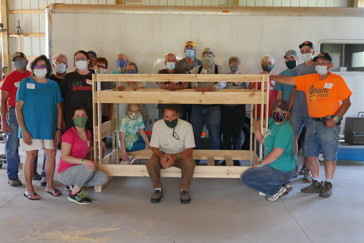 A core group of experienced volunteers and staff from Lowe's Home Improvement help guide people through building their first bed.