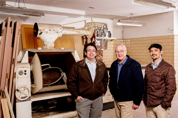 Raymond Minervini Jr., Don Coe, J. Robert Sirrine in front of an old Hobart dough mixer that was used during the Traverse City State Hospital era. / Elizabeth Price