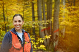 Katie Armstrong stands in front of a red maple clump marked to cut as part of a hardwood thinning.