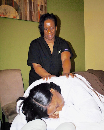 Margaret Kirk, owner of Massage Green SPA, gives her daughter, Tyla Wade, a shoulder massage in early February.