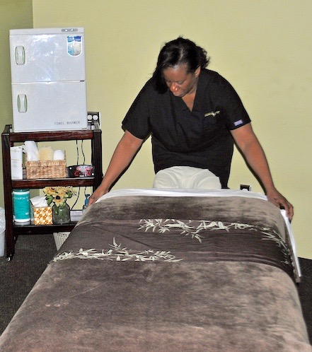 Margaret Kirk straightens the bedding in the couples massage room at her business, Massage Green SPA. A grant from the Small Business Community Loan and Grant Fund enabled Kirk to purchase new equipment carts.