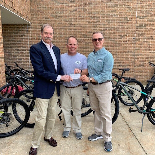BIke Friendly Kalamazoo's President Paul Selden, left, presents Portage West Middle School's Physical Education Teacher James Righter and Assistant Principal Kevin Doerfler with BFK's Bike-Booster Mini-Grant.