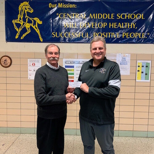 President Paul Selden (left) presents Portage Central Middle School Gym Teacher John Dunlop with a BFK Bike-Booster Mini-Grant on Oct. 30. PSMS has taught more than 1,200 middle-schoolers. More than 30 of them did not know how to ride a bicycle.