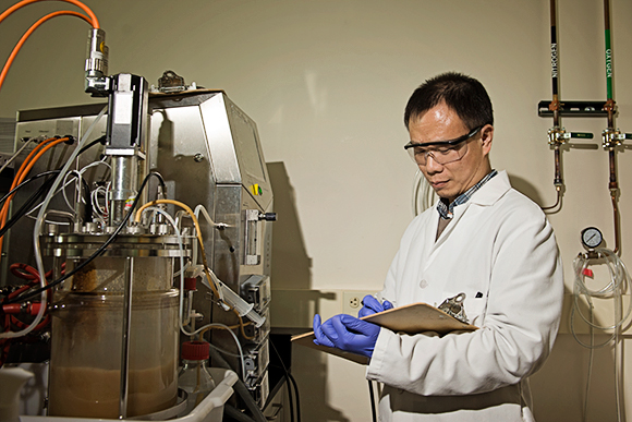 Lin Bau, Senior Research Scientist, checks a fermenter used to synthesize peptides.
