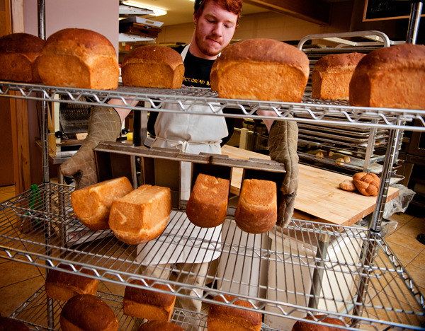 The Victorian Bakery assitant baker Cory Snyder places warm loaves  of oatmeal bread on the cooling rack