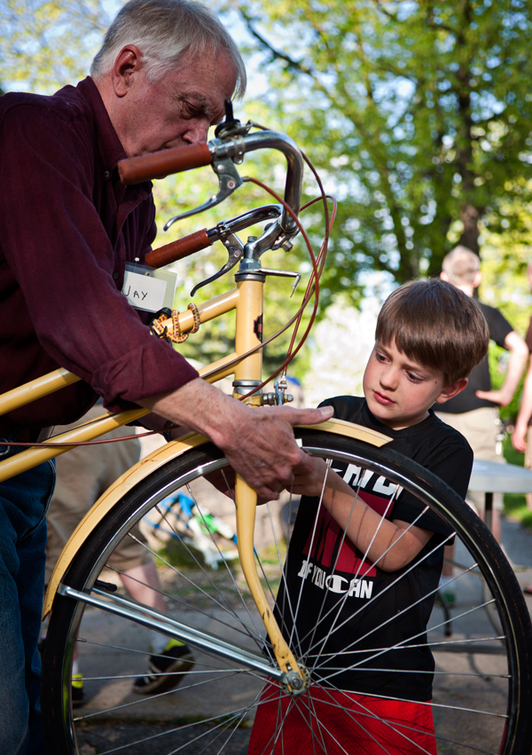 James Balkema, 5, right, tightens a screw on his bike with the help of Open Roads volunteer Jay Baumer.
