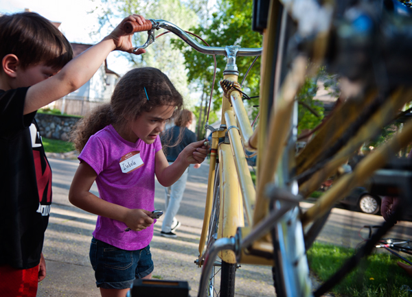 Isabella Santos-Pye, 6, tightens a screw on a bike she is helping to fix up at Open Roads in the Edison neighborhood.