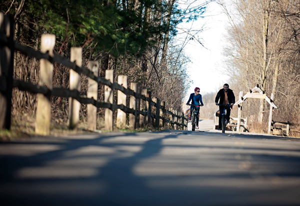 Melanie Brothers, left, and Paul Schnieder  bike down the trail near Celery Flats in Portage, MI