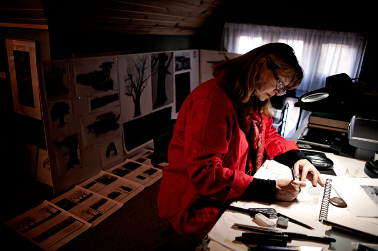 Linda Rzoska, owner of Ninth Wave Studio, works on a recent piece in her upstairs workspace.