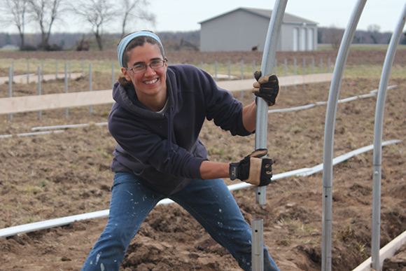 Ruthie Thompson installs the first of five hoop houses in 2013.