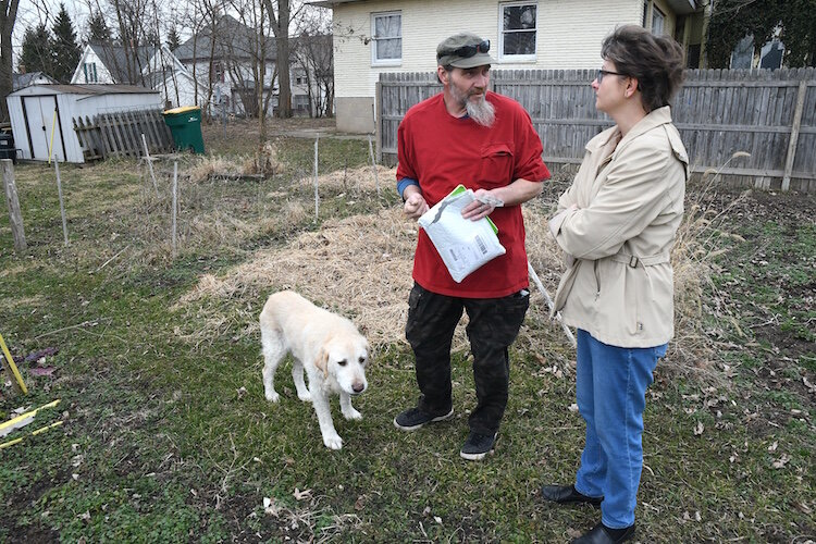 Thomas Hart, main caretaker of the Fremont Garden, and Jackie MacCannell, volunteer, discuss plans for this year's garden. Also seen in the photo is Jake, the garden's mascot.