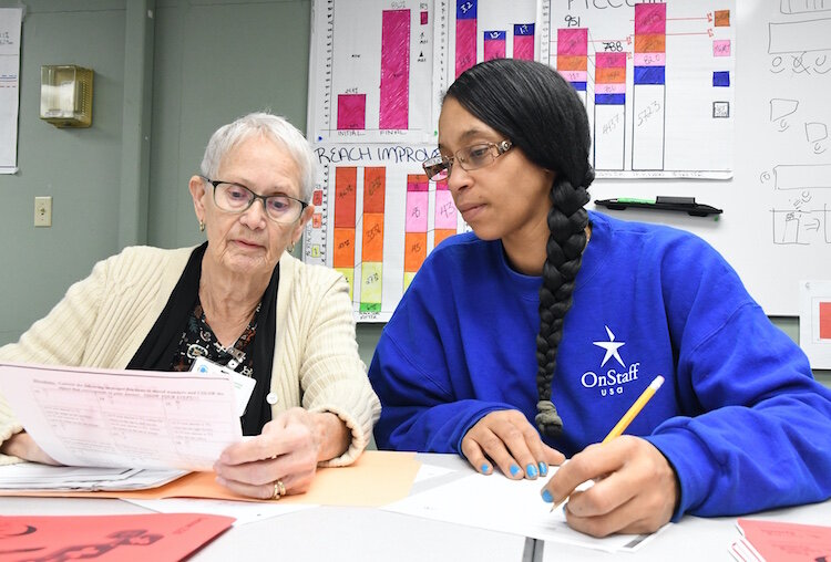 Carol Poole, GED instructor for Battle Creek Public Schools, works with Lilleana Bottom, Denso temporary employee, on Mathematics work.