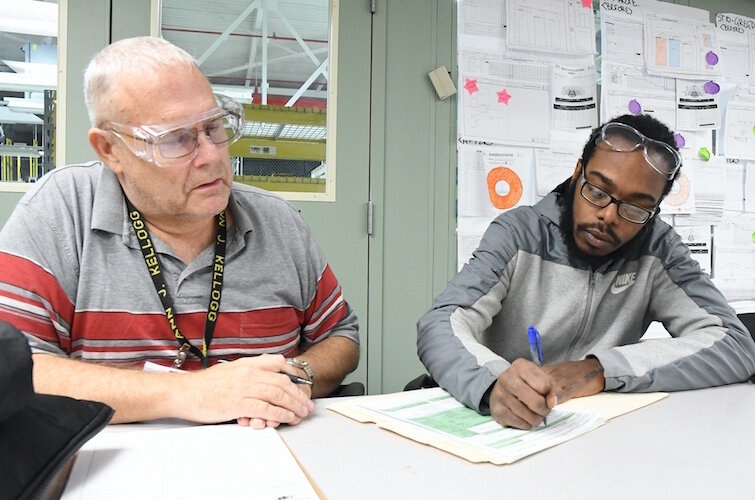 Barry Linscott, GED instructor for Battle Creek Public Schools, assists Deandre Muldrow, Denso employee, enroll in the GED program.