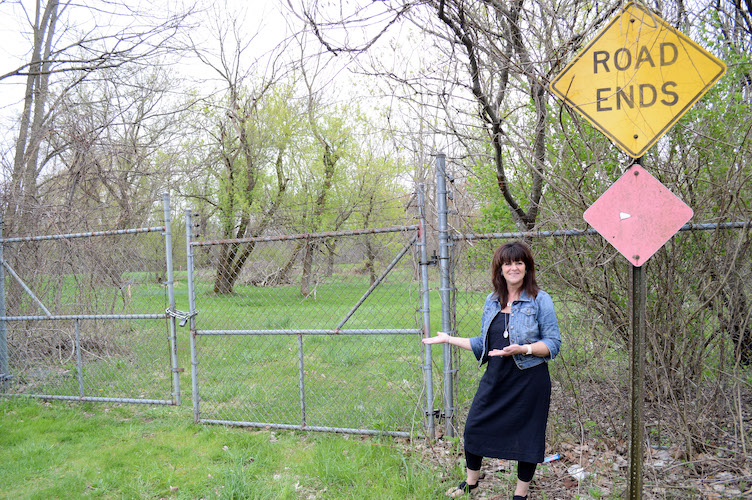 Galesburg mayor Lori West at the end of Mill Street. For the Kalamazoo River Valley Trail length through Galesburg, the gates will come down and the trail will meander through the trees along the Kalamazoo River.