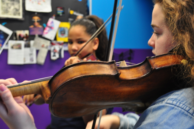 Samira, a 4th grade Kalamazoo Public School student, plays a piece for her teacher, Alexis Terrian, a Western Michigan University sophomore.