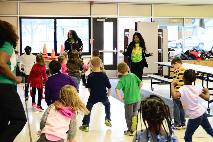 "From left, Operation Fit coordinators Mariama Wurie, Tamera Gibbs and Emirrora Austin lead LaMora Park kindergarten students in a ""Brain Break."" Photo by Mark Wedel"