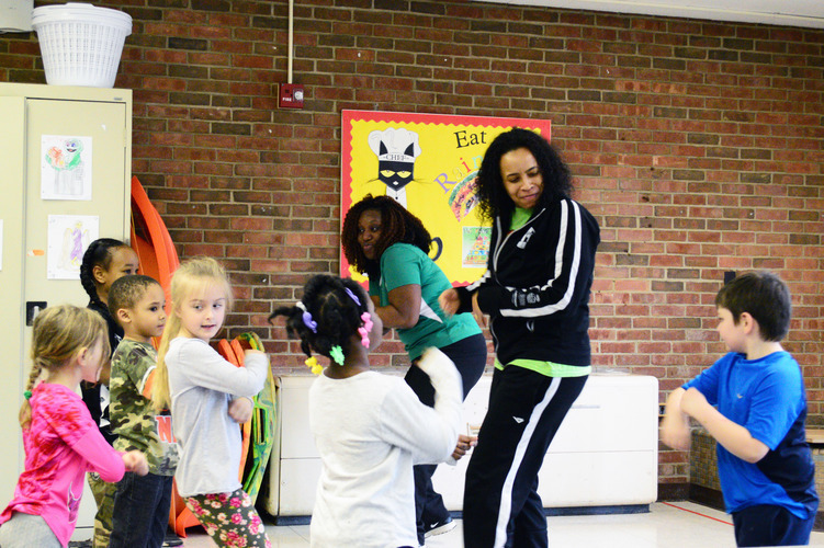 "Operation Fit's Mariama Wurie and Tamera Gibbs doing the ""Cha-Cha Slide"" with LaMora kindergarteners. Photo by Mark Wedel"