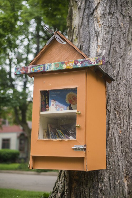 This Little Free Library has a charming Vine-ish twist with its bright orange paint and attached to a tree.