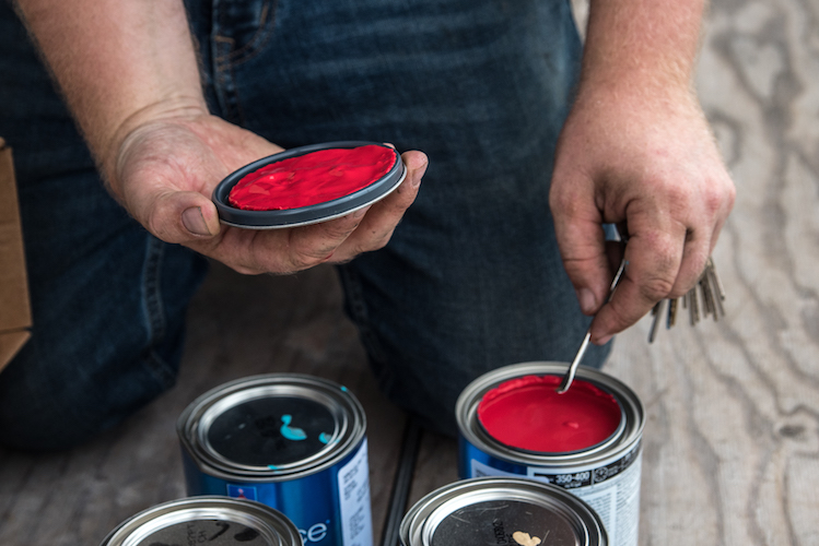 Patrick Hershberger mixes his paints for a new mural going up in the neighborhood. Photo by Fran Dwight