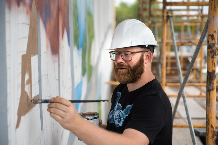 Patrick Hershberger at work on a new mural for the Edison neighborhood. Photo by Fran Dwight