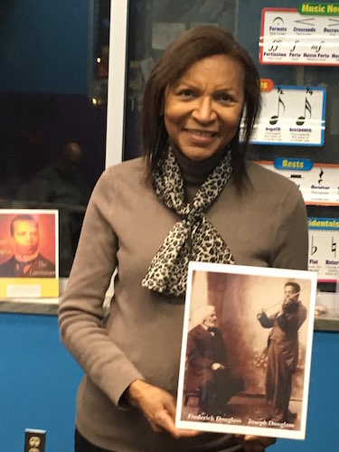 Bertha Barbee-McNeal, Artistic Director and Piano Teacher at the Helen Fox Gospel Music Center, holds a prized photo of Joseph Douglass, accomplished violinist and grandson of abolitionist Frederick Douglass after whom the Douglass Community Associat