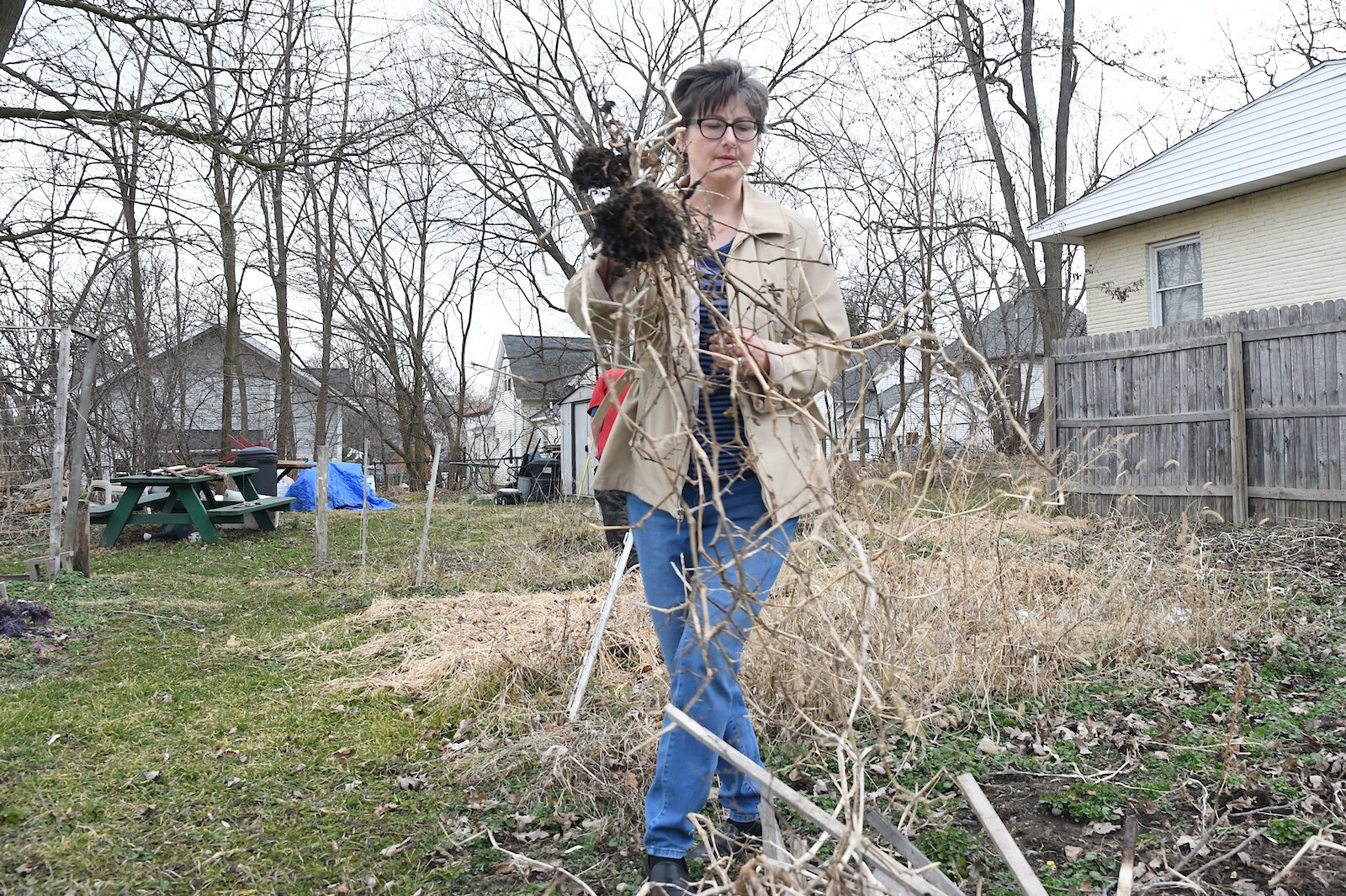 Jackie MacCannell cleans up refuse at the Fremont Garden.