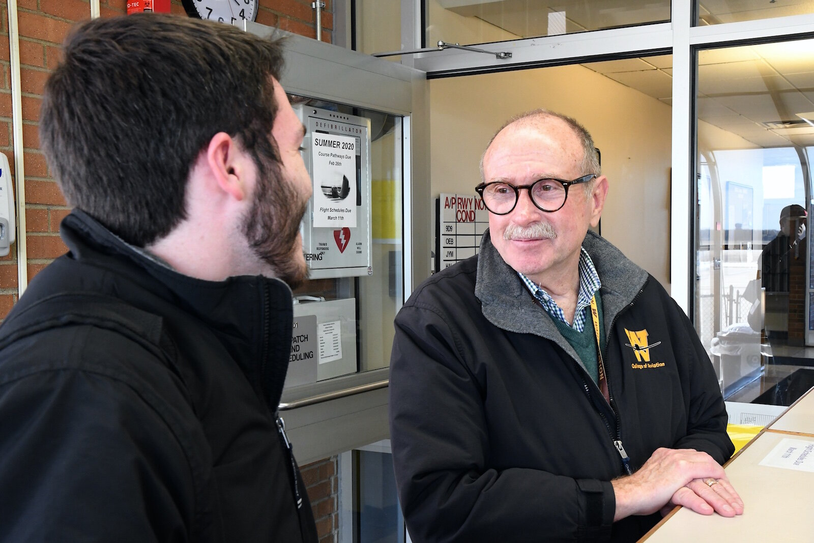 Dave Powell, dean of Western Michigan University's College of Aviation, right, talks with William Gaffney, a graduate and instructor.