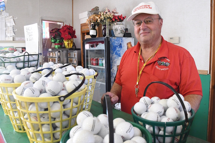 Jeff Heppler with buckets of golf balls for driving range.