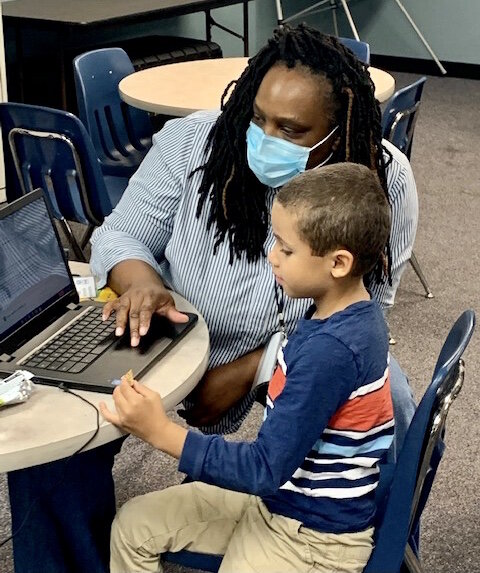 An instructor helps in early elementary student with an online class in New Genesis Academic Hub.