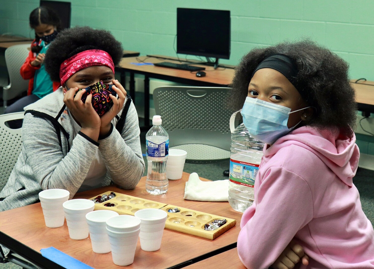 Two girls wear masks while playing games at the Boys & Girls Club.