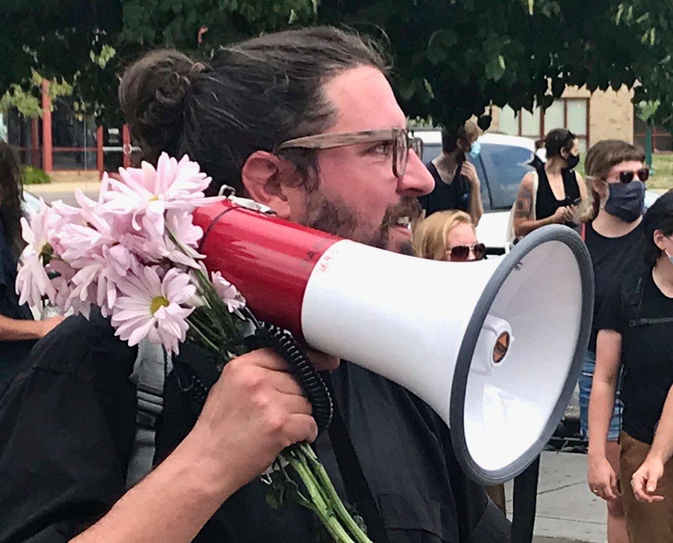 Using a megaphone adorned with the flowers, Rev. Nathan Dannison speaks to counter-protesters on Saturday, Aug. 15, 2020 in downtown Kalamazoo.