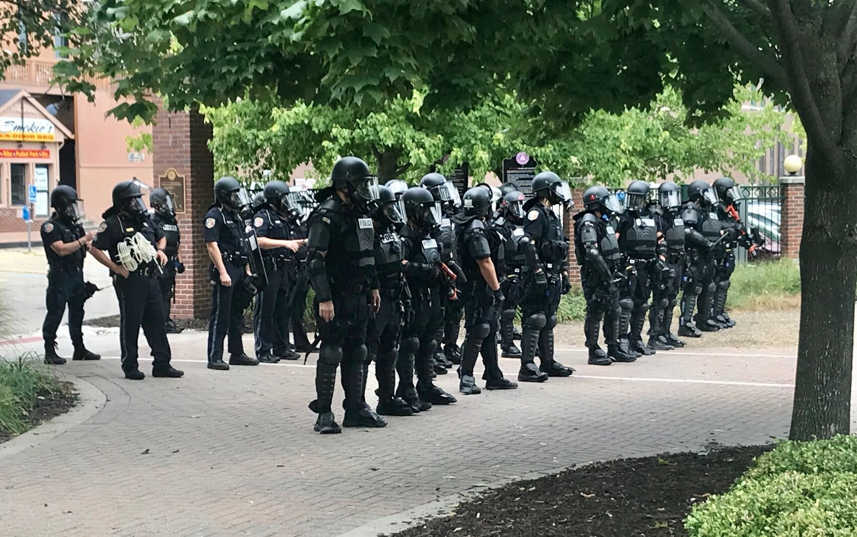 Police in riot gear form a line just inside the east entrance of Arcadia Creek Festival Place. Other officers entered at other points in order to clear the area.