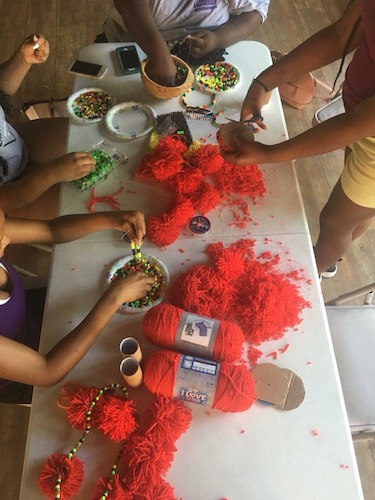 Rootead Youth Dance Company preparing for a show by creating and designing their own unique African Dance belts and accessories.