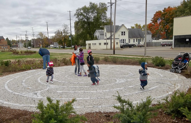 "Youngsters are shown in October of 2012 enjoying a game that was included in the ""interim landscaping"" of native flowers on the site of the former Kalamazoo Creamery Company building after it was demolished at Lake and Portage streets."