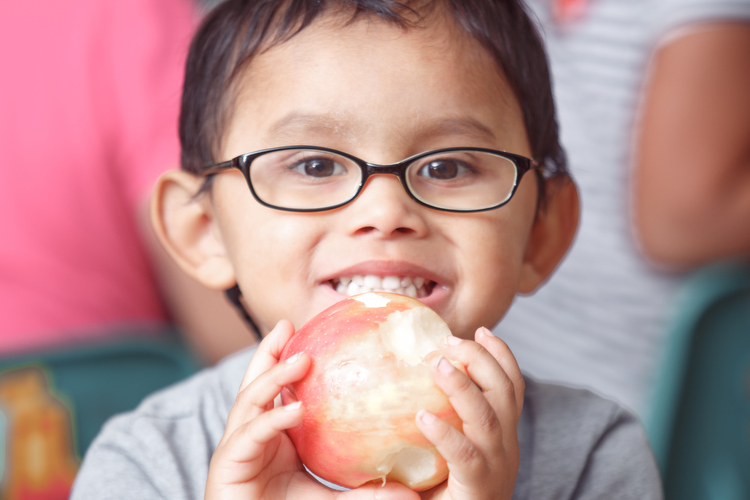 Enjoying a Michigan apple for lunch at the Head Start Program in Sparta. Photo by Autumn Johnson
