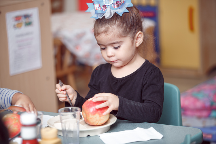 Enjoying a Michigan apple for lunch at the Migrant Head Start program. Photo by Autumn Johnson