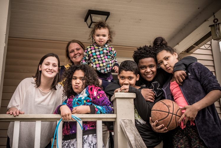 Nicole Miller gathers with Samantha Drew and her family at their home in the Edison neighborhood. Photo by Fran Dwight
