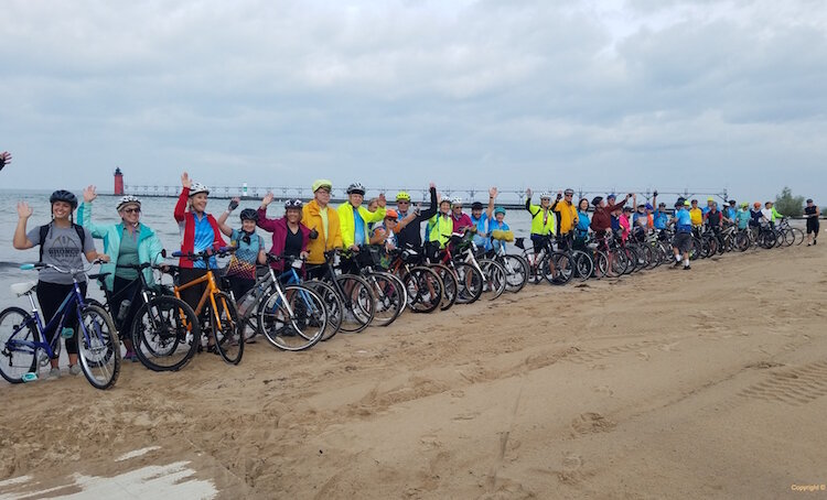 Riders dip their rear tire in Lake Michigan before taking off for Lake Huron