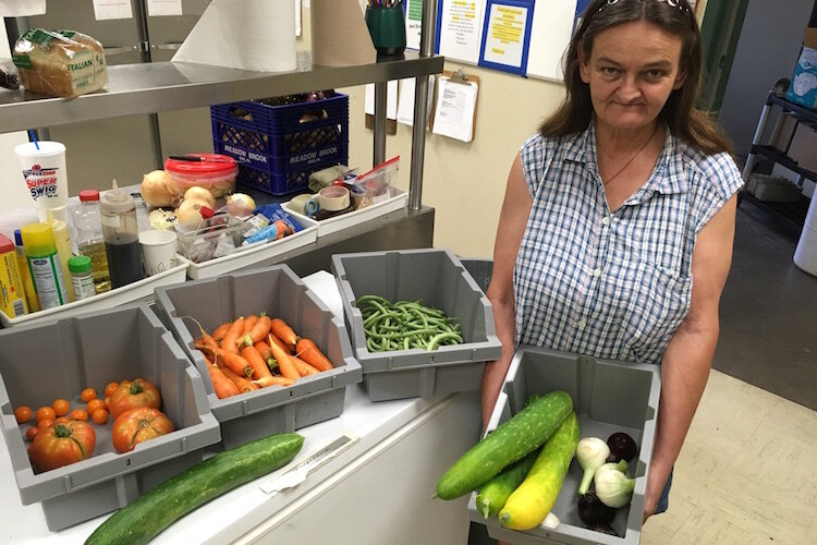 Linda, a consumer of the SHARE Center, stands in the organization's kitchen and holds a bowl containing some of the vegetables grown in the garden.