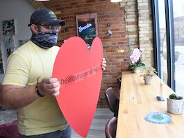 Tristan Bredehoft of Café Rica puts up a racial healing heart in the café's front window.