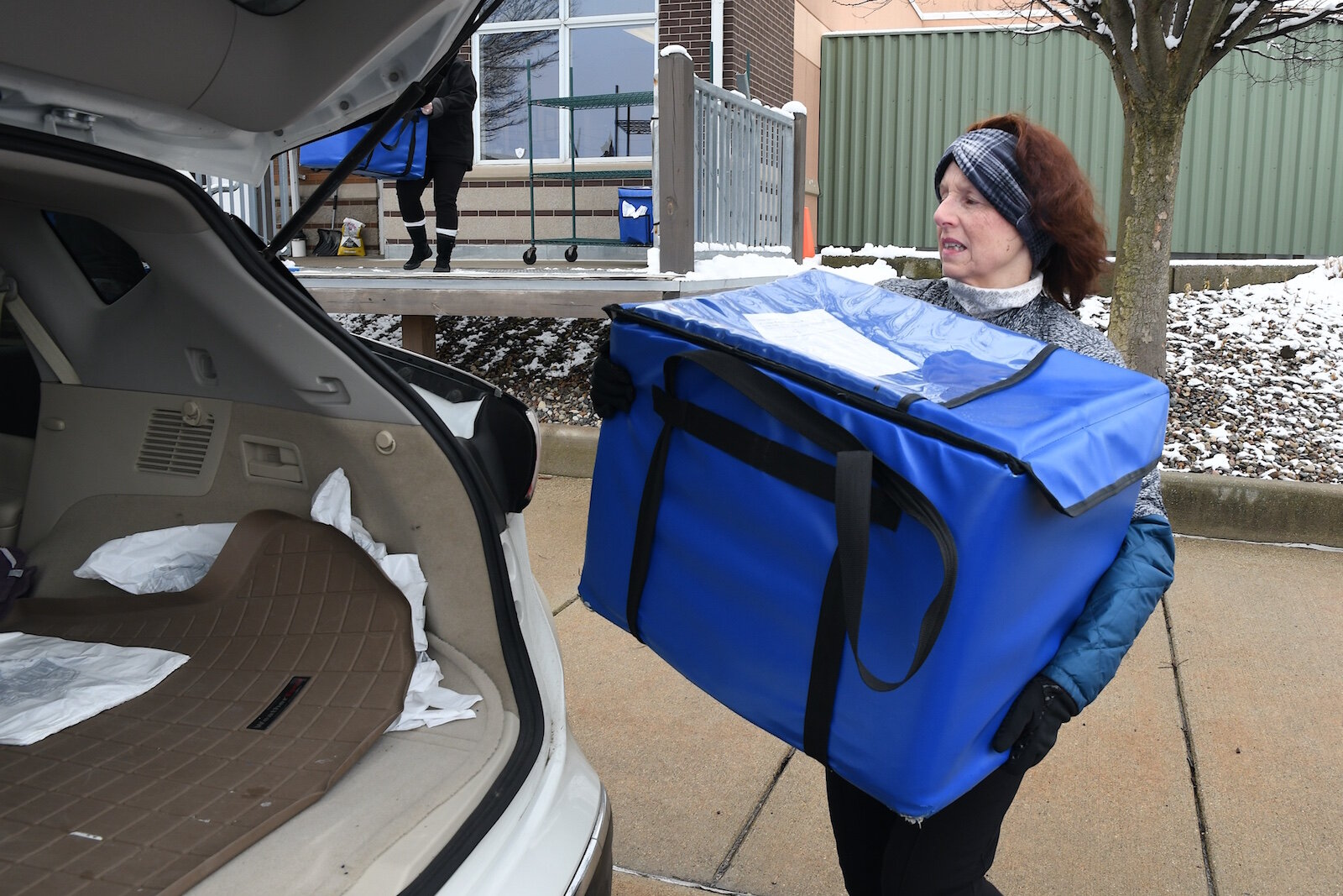 Theresa Burke loads up meals to be delivered into her vehicle.