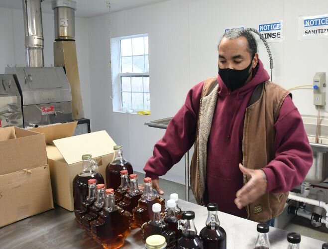 Robert Williams, Environmental Technician, points out some of the maple syrup produced in the sugar shack at the Pine Creek Indian Reservation.