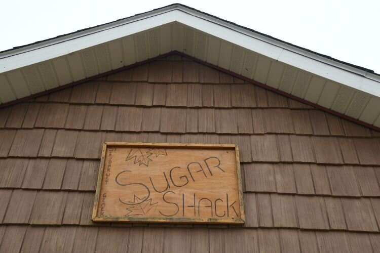 Sign over the doors at the front of the sugar shack.
