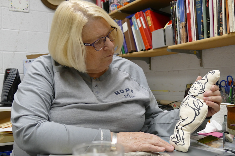 Jody Owens, secretary of the board for the Historical Society of Battle Creek looks closely at a Twinzy Toy elf.