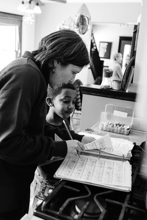 Molly Mechtenberg-Berrigan, one of the Peace House founders, helps a young person with homework.