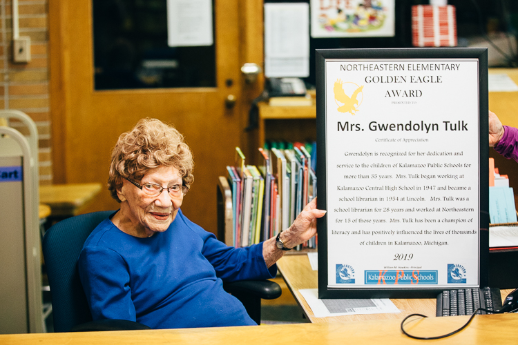Former Northeastern Junior High School Librarian Gwen Tulk, who just turned 102, was honored at a special ceremony in her old library in April. Here she sits at her former librarian desk.