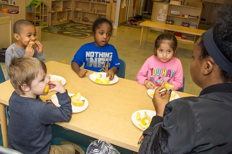 Nina Smith and children in the YWCA Children's Center eat an apple for a snack. Photo by Susan Andress