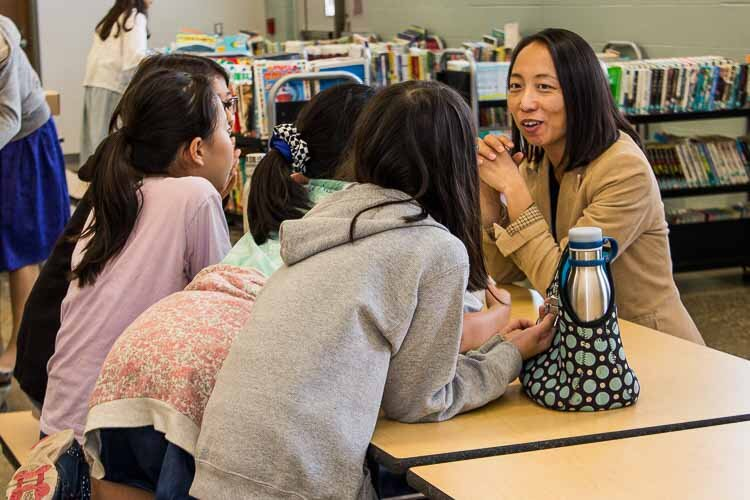 Teacher Michiko Yoshimoto chats with students at lunch.